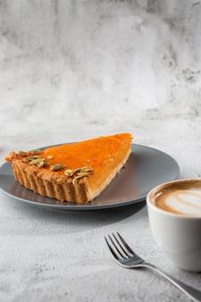 Porcja wyśmienicie jaskrawej pomarańczowej dyni otwarty kulebiak na popielatym talerzu, dekorującym z dyniowymi ziarnami z deserowym rozwidlenia zakończeniem, odgórny widok. jasne tło marmurowe. skopiuj miejsce pionowy. menu dla kawiarni
