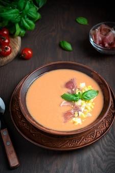 Porcja zimnej hiszpańskiej zupy salmorejo ze zmiksowanych surowych pomidorów zajadana z szynką podawana na stole