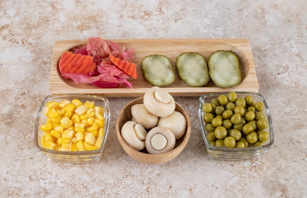Porcje świeżych i marynowanych warzyw na marmurowej powierzchni.