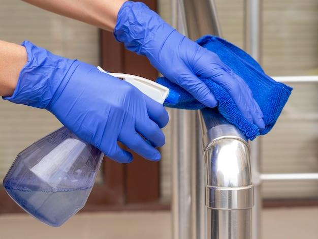 Poręcz dezynfekowana jest rękami w rękawiczkach chirurgicznych