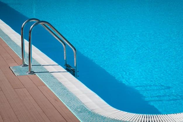 Poręcz na basenie. basen ze schodami w tropikalnym kurorcie. wodny basen ze słonecznym odbiciem. stalowa poręcz, pływanie, lato, podróże.