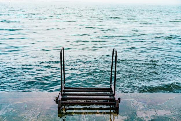 Poręcze schodów do błękitnego morza. metalowe schody. schody wejście do falistego morza. wał przeciwpowodziowy. woda z falami. lato. brak ludzi na promenadzie. nikt. pusty. wietrzny. balustrada