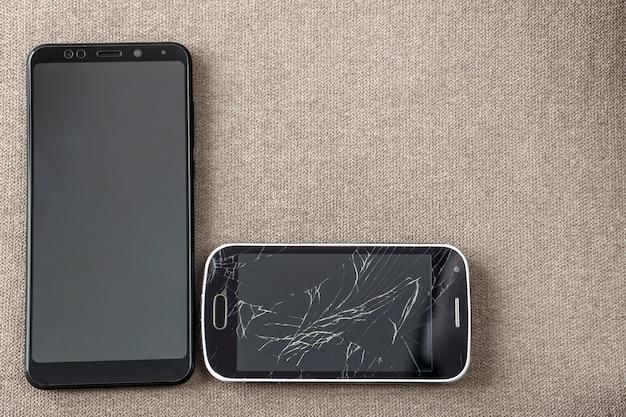 Porównanie dwóch czarnych telefonów komórkowych, starego telefonu komórkowego z pękniętym ekranem i nowego nowoczesnego na jasnym tle tkaniny.