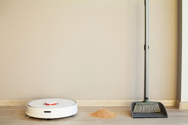 Porównanie robota czyszczącego i miotły w jasnym pokoju