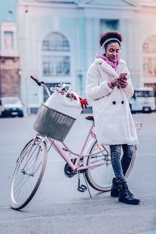 Porozmawiajmy. wesoła brunetka kobieta opierając się na rowerze, patrząc na ekran swojego gadżetu
