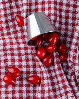 Porozrzucane jagody derenia z mini wiadra na pikniku