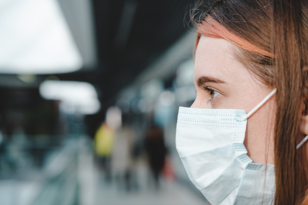 Porrait kobiety z maską w miejscu publicznym. koronawirus, koncepcja zapobiegania rozprzestrzenianiu się covid-19, odpowiedzialne zachowanie społeczne obywatela