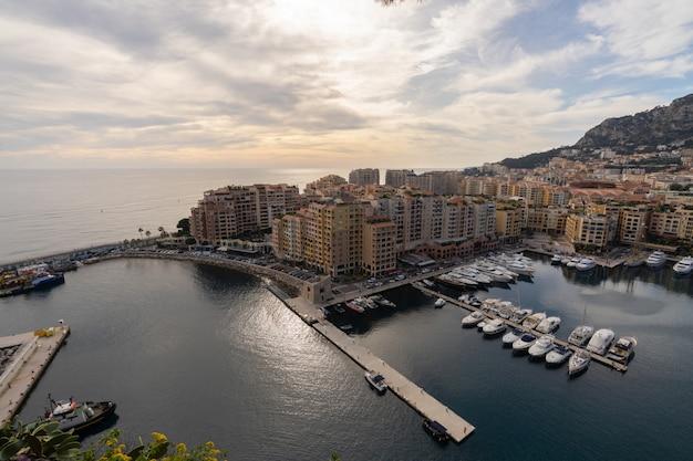 Port de fontvieille w azur wybrzeżu na wschodzie słońca z niebieskie niebo chmurą. cenne apartamenty i port z luksusowymi jachtami w zatoce, monte carlo, monako, europa