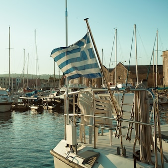 Port, grecka flaga i łodzie