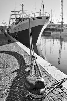 Port i zawiązany statek na nabrzeżu, rimini, włochy. fotografia czarno-biała