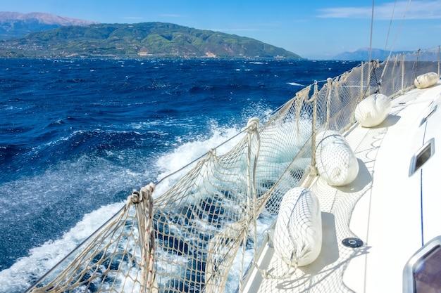 Port jachtu żaglowego z barierką ochronną i odbijaczami. głęboki błękit morza i morska piana