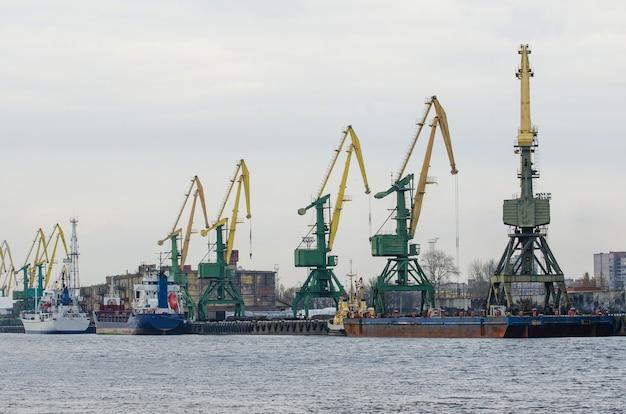 Port morski z dźwigami, statki na molo do załadunku towarów.