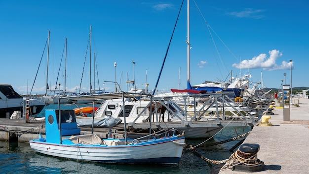Port morza egejskiego z wieloma zacumowanymi jachtami i łodziami, bezchmurna pogoda w nikiti w grecji