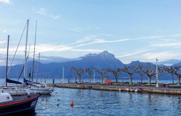 Port torri del benaco. miasto położone jest na środkowym wschodnim wybrzeżu jeziora garda, na granicy z gardą na południu i brenzone sul garda na północy. w tle monte pizzocolo