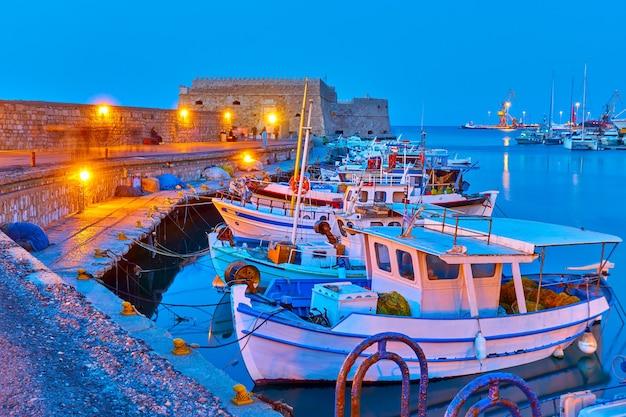 Port w heraklionie ze starymi łodziami rybackimi o zmierzchu kreta, grecja