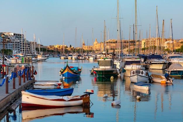 Port w valletcie z jachtami i wielokolorowymi łodziami rybackimi luzzu z oczami, kościołem i fortecą, oświetlone światłem zachodu słońca, malta