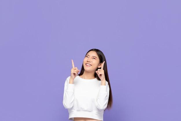 Portait śliczna uśmiechnięta młoda azjatycka kobieta wskazuje ręki up i patrzeje copyspace above w purpurach odizolowywał ścianę