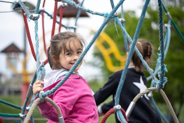 Porter małej uśmiechniętej dziewczyny bawiącej się na placu zabaw.