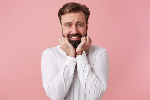 Porterait młodego przystojnego brodatego mężczyzny, z szeroko otwartymi ustami, gryzie paznokcie, przestraszony, odizolowany na różowym tle.