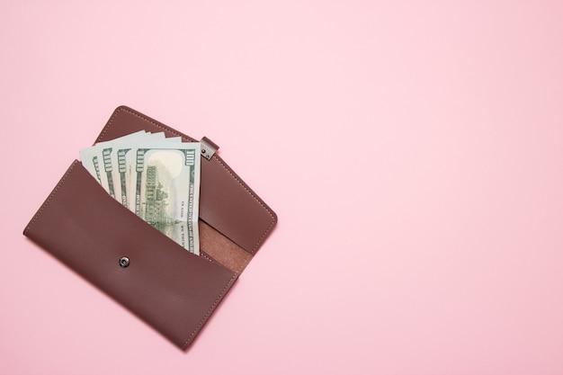 Portfel damski z pieniędzmi na różowym tle. widok z góry.