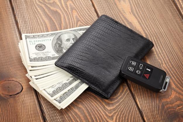 Portfel na pieniądze i kluczyk samochodowy na drewnianym stole