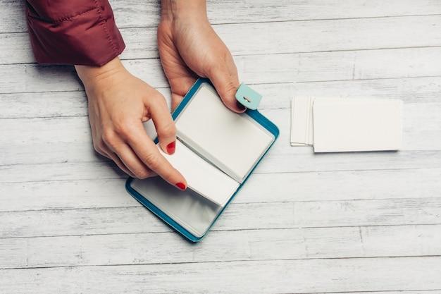 Portfel na wizytówki w rękach kobiet widok z góry drewniany stół biurowy