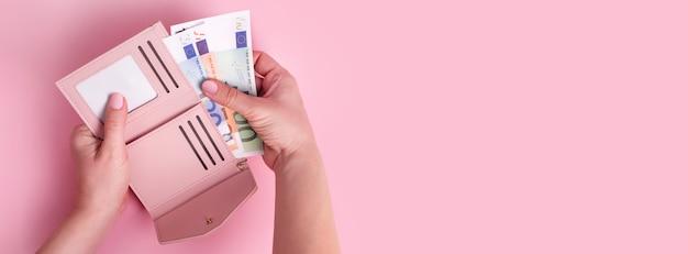 Portfel trzymając się za ręce. różowy skórzany portfel z pieniędzmi euro w rękach kobiet.