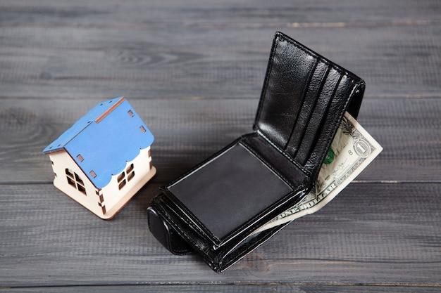 Portfel z banknotami dolarowymi i domem. koncepcja zakupu domu home