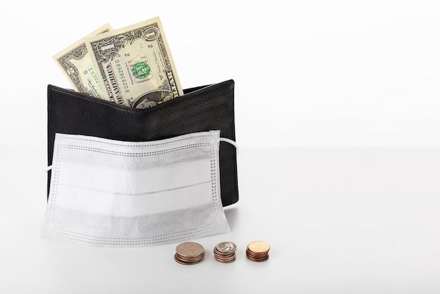 Portfel z dolarem, centami i izolowaną maską ochronną. koncepcja globalnego kryzysu i spadających dochodów z powodu pandemicznego koronawirusa covid-19.