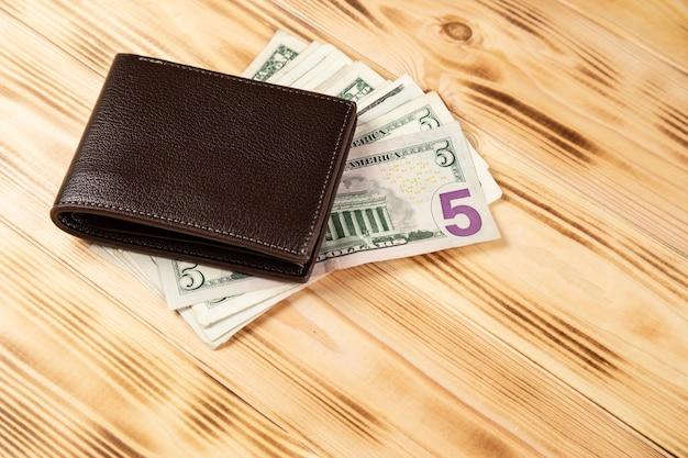 Portfel z pieniędzmi na powierzchni drewnianej