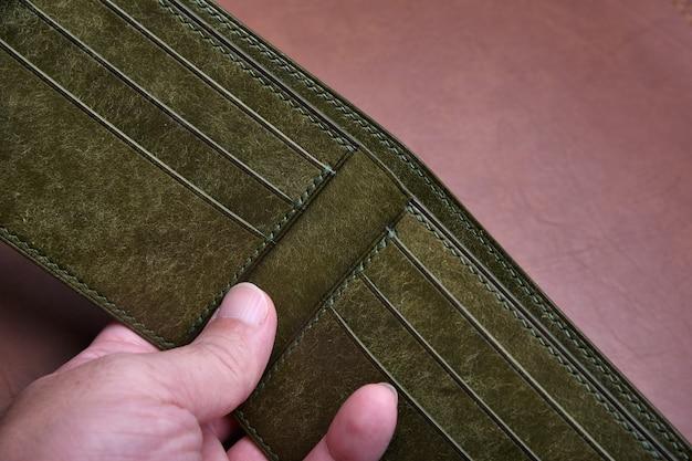 Portfel ze skóry naturalnej, detal wewnątrz rzemieślniczego portfela w kolorze oliwkowozielonym garbowanym roślinnie, moda męska i akcesoria.