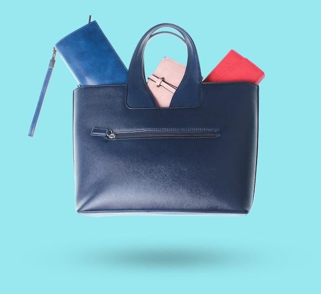 Portmonetki 3d w skórzanej torbie na białym tle na niebieskim tle