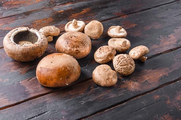 Portobello i grzyby shiitake na starym drewnianym stole, widok z boku miejsca na tekst.