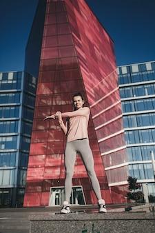 Portowa dziewczyna w modnej odzieży sportowej robi ćwiczenia jogi fitness na ulicy, sporty na świeżym powietrzu, miejski styl
