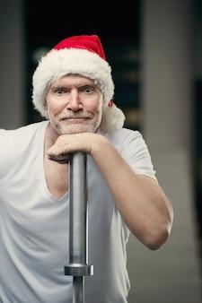 Portraite starszego mężczyzny w kapeluszu santa clause w siłowni sylwester i koncepcja bożego narodzenia