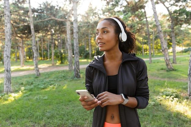 Portret 20s brunetka kobieta ubrana w czarny dres i słuchawki, używając telefonu komórkowego podczas spaceru po zielonym parku
