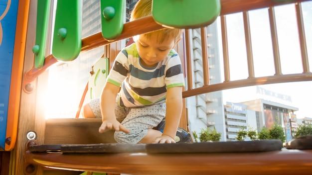 Portret 3 lat małego chłopca spaceru i czołgania się na wysokim drewnianym moście na plac zabaw dla dzieci w parku. dzieci bawiące się i bawiące na placu zabaw