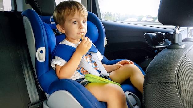 Portret 3 lat toddler chłopiec siedzi w foteliku w samochodzie i jedzenie ciasteczek. dzieci podróżujące samochodem
