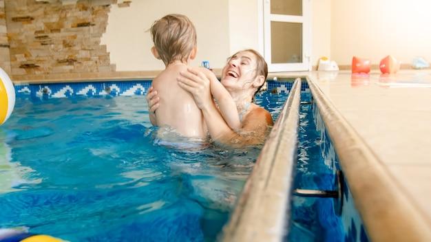 Portret 3 lat toddler chłopiec z młodą matką pływanie w krytym basenie. dziecko uczy się pływania i uprawiania sportu. rodzina ciesząca się i bawiąca się w wodzie?