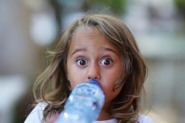 Portret 4-letniej dziewczynki wody pitnej z plastikowej butelki