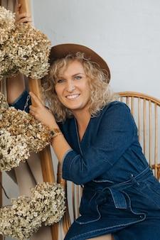 Portret 40-letnia piękna blondynka w kapeluszu. zawód kwiaciarz i dekorator wnętrz. śmieje się z białym uśmiechem, w kapeluszu, wśród dekoracji kwiatów, patrząc w kamerę. naturalny wystrój