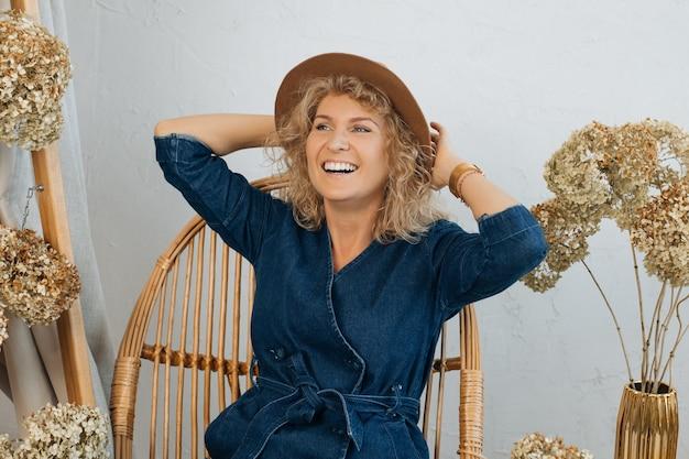 Portret 40-letnia piękna blondynka w kapeluszu. zawód kwiaciarz i dekorator wnętrz. śmieje się z białym uśmiechem w kapeluszu, wśród dekoracji z kwiatów, odwracając wzrok. naturalny wystrój