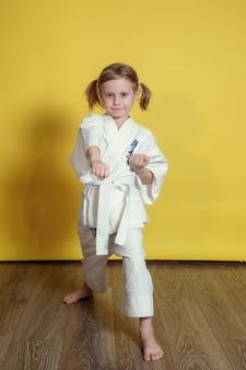 Portret 5-letniej dziewczynki w kimonie ćwiczącej karate na tle żółtej powierzchni w domu