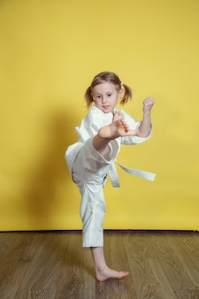 Portret 5-letniej dziewczyny kaukaski w kimono praktykujących karate na żółtym tle w domu
