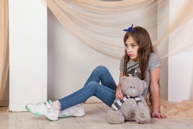 Portret 7-8 letnia dziewczynka w swobodnym stroju przy kominku z napisem teddy bear for you