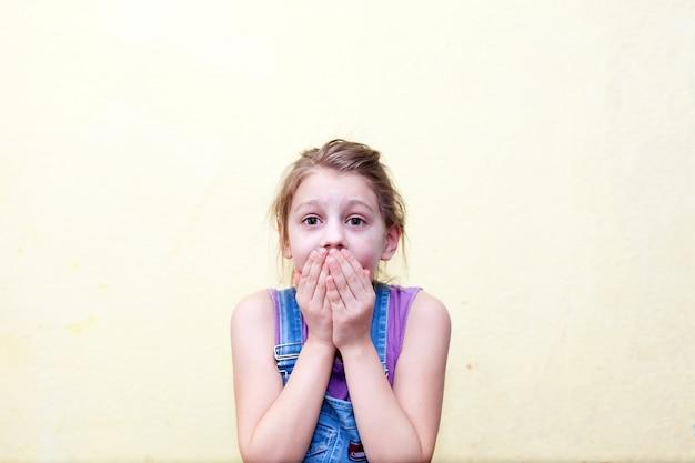 Portret 8-letniej dziewczynki na żółtej ścianie, przestraszona, zakrywająca usta rękami