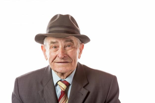 Portret 90-letni starszy mężczyzna w retro kapeluszowej patrzeje kamerze odizolowywającej na bielu