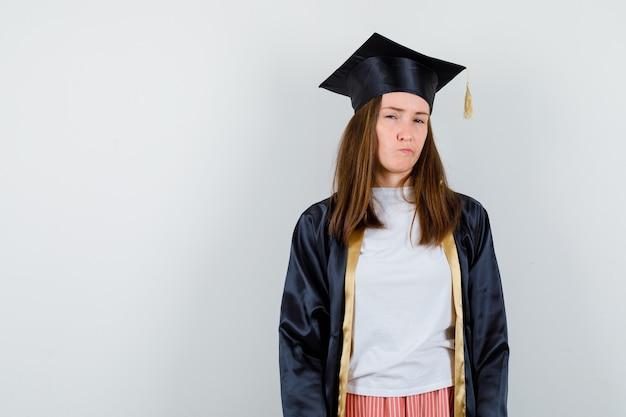Portret absolwentka patrząc na kamery, zakrzywione usta w akademickim stroju i zamyślony widok z przodu