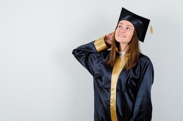 Portret absolwentka pozowanie, patrząc w akademicką sukienkę i patrząc z nadzieją na widok z przodu