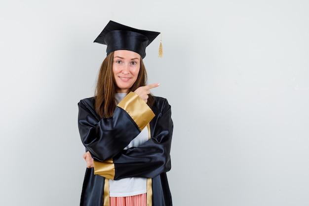 Portret absolwentka wskazując w prawo w akademickim stroju i patrząc pełen nadziei widok z przodu